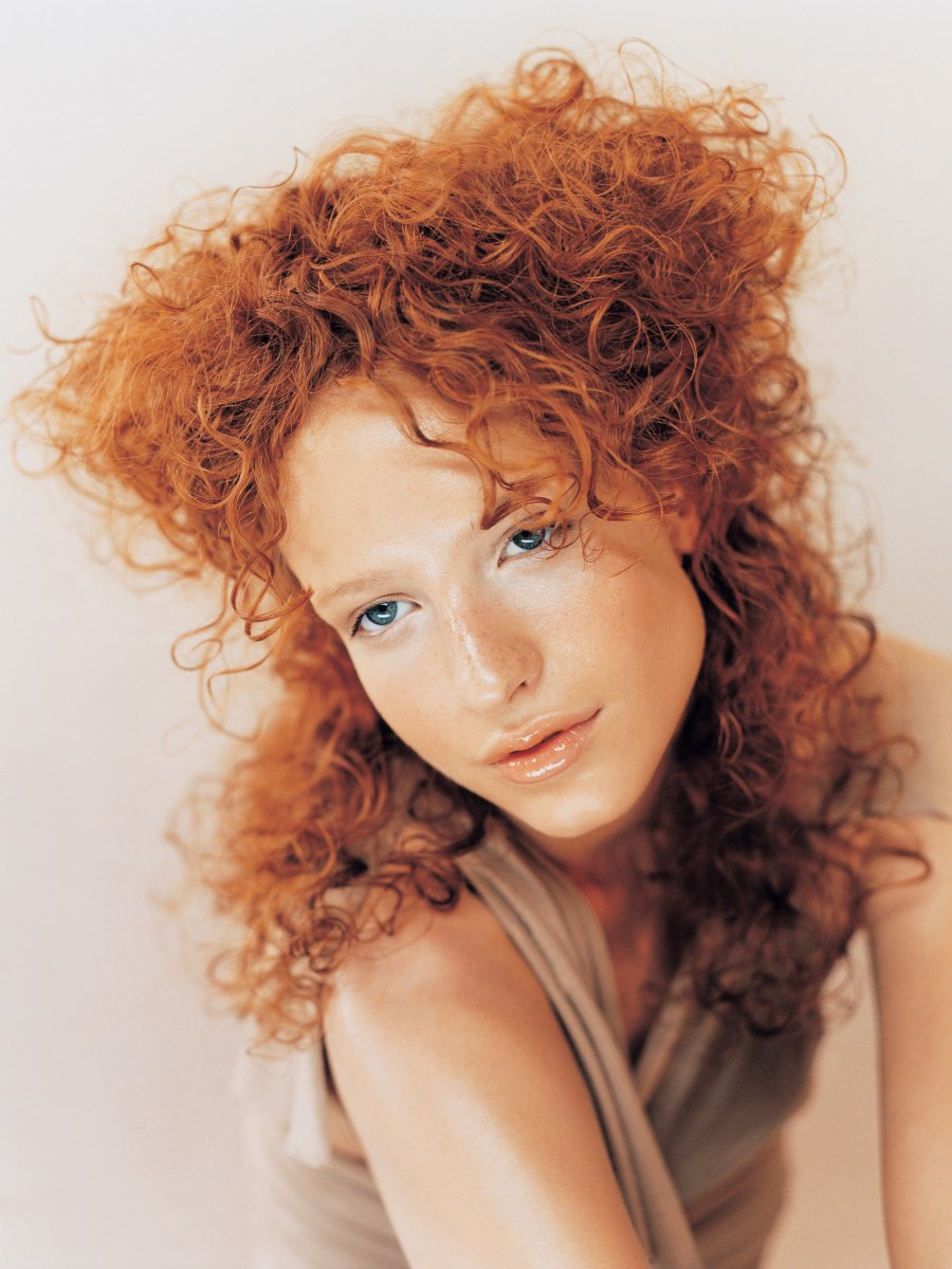 Red Hair With Curls That Spread Out Over The Shoulders
