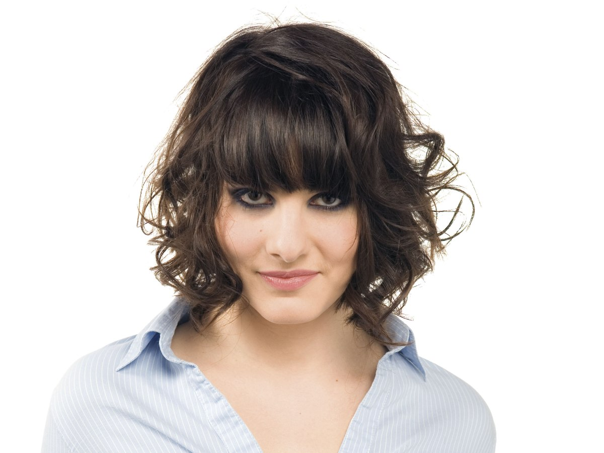 Chin Length Bob With Curls Straight Bangs And A Side Part