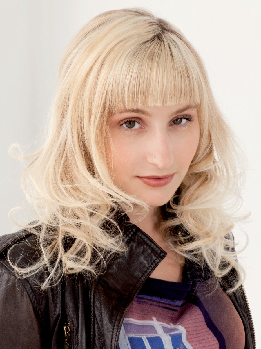 Blonde Hair With Straight Bangs And Curls Around The Shoulders