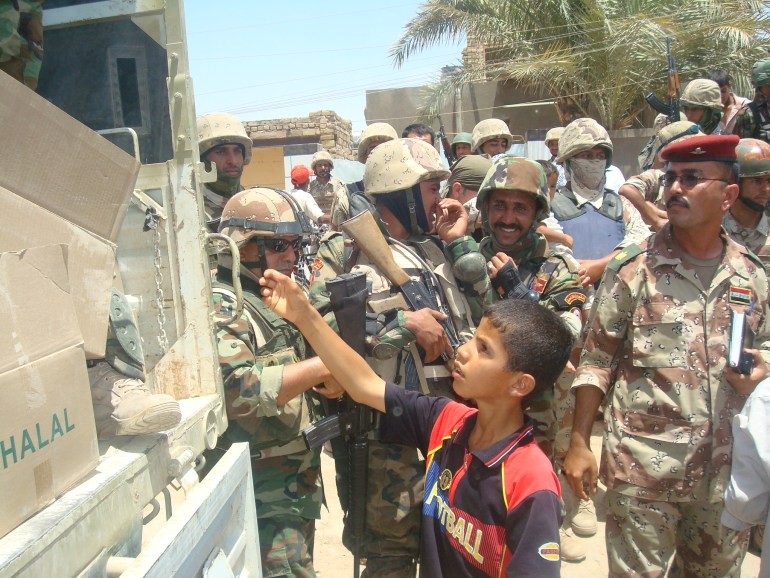 "An Amarah boy reaches out for a Halal meal, as Iraqi army soldiers look on June 22. The IA-led humanitarian assistance mission was a huge success, said Col. Ali Ayid, 10th IA Division civil affairs officer. IA soldiers handed out 8,316 meals to 12 different neighborhoods in Amarah. ""We had a large turnout and all of the citizens looked extremely grateful for assistance,"" said Ayid."
