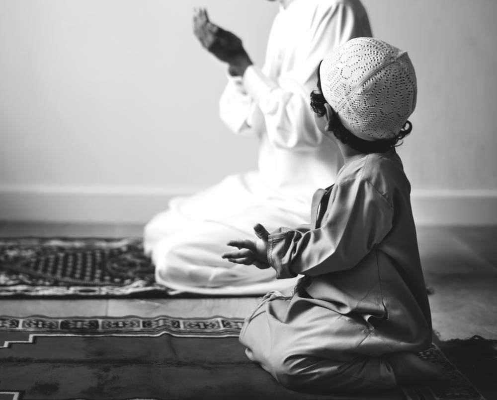 father son on prayer mat