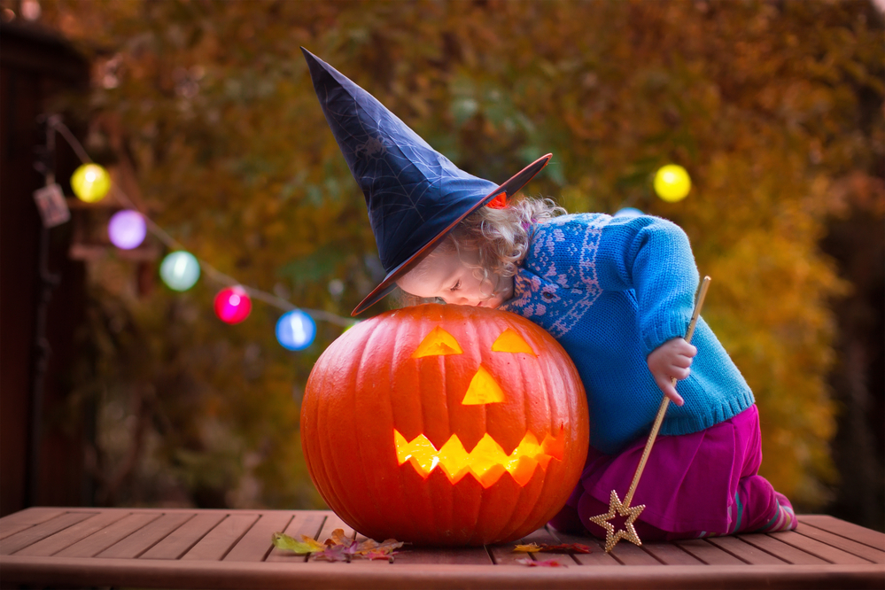 halloween pumpkin and little girl dressed as witch