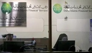 Staff work behind the glass at Dubai Islamic Financial Services at the stock market in Dubai