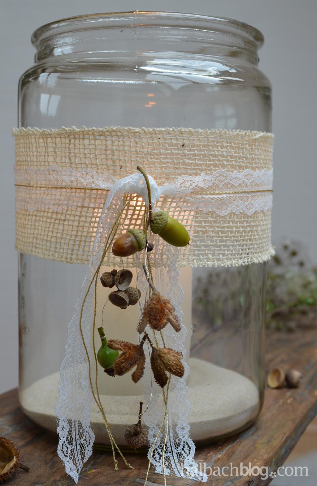 Herbstdeko-Idee halbachblog: Windlicht mit Jutenband, feiner Spitze, Goldkordel, Eicheln und Bucheckern