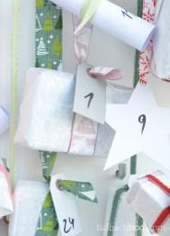 DIY-Idee halbachblog: Adventskalender am Kleiderbügel mit angeknoteten Bändern in Rosa, Rot, Korall, Mint, Hellgrün, Petrol mit Päckchen und Hangtags