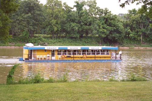 The Grand River Belle, a river boat cruise drifts along the river as guests on board sit on the deck, enjoying the scenery