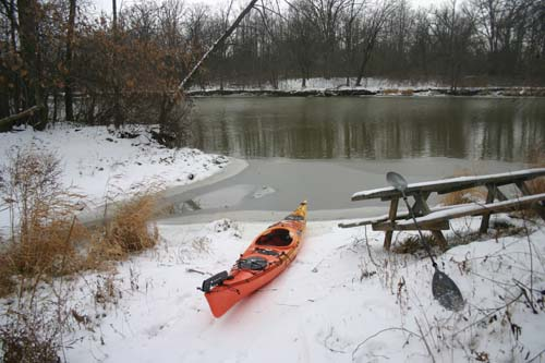 A snowy bank along the grand river stands as contrast to the bright orange kayak that sits upon its shore