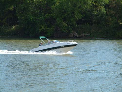 A speed boat races down Grand River, the children on board smile broadly