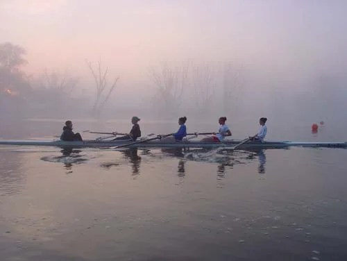Rowers battle early morning fatigue as they train in the foggy early morning along the Grand River