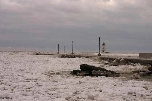 Sheets of snow and ice pile together along the pier
