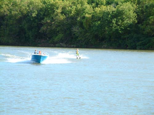 A young family tows their father behind them during a family outing of water skiing on Grand River