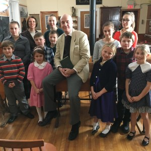 A picture of a class of children and their teacher in a one room schoolhouse