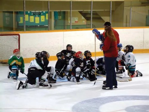 Children listen attentively as these hockey volunteers offer advice on Hockey and life