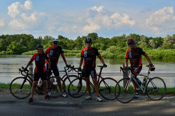 a group of on road cyclists, stoping by the river with their bikes