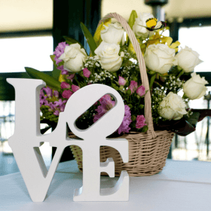 White block letters that spell love sit on table in front of a basket of flowers