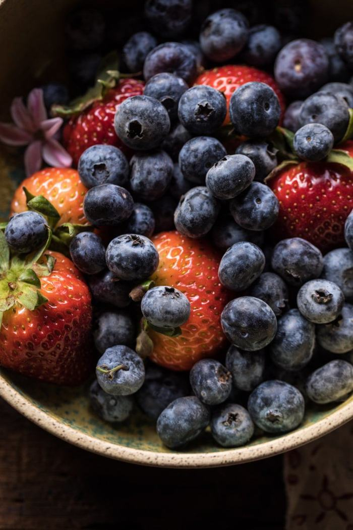 close up overhead photo of strawberries and blueberries