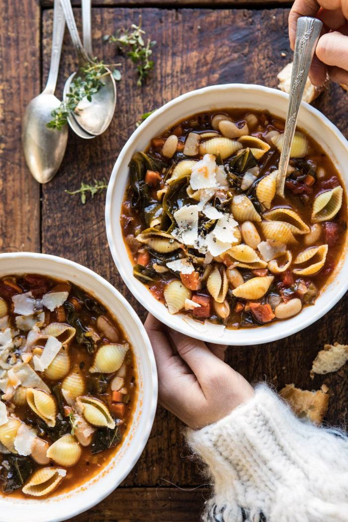 overhead photo of Instant Pot Pasta e Fagioli with hands on bowl
