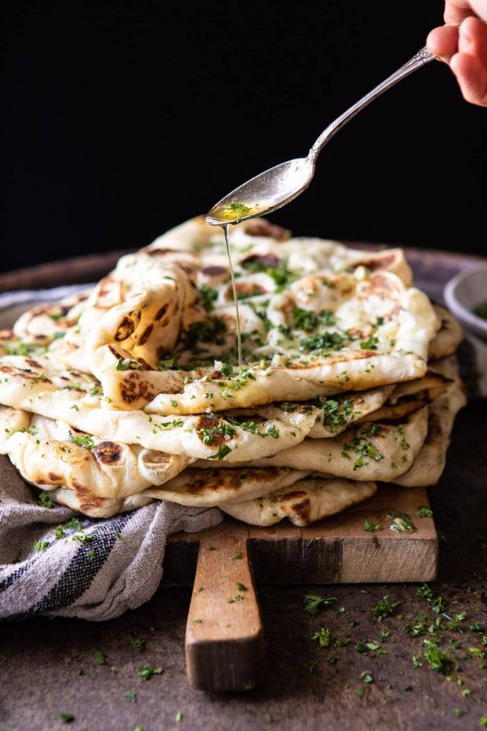 side angle photo of drizzling butter over Herbed Garlic Butter Naan