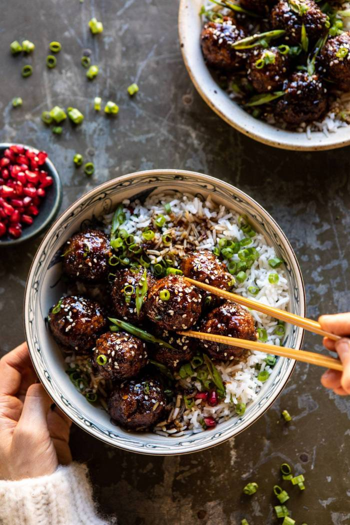 overhead photo of Weeknight Sticky Ginger Sesame Chicken Meatballs with hands on bowl and chopsticks picking up meatball
