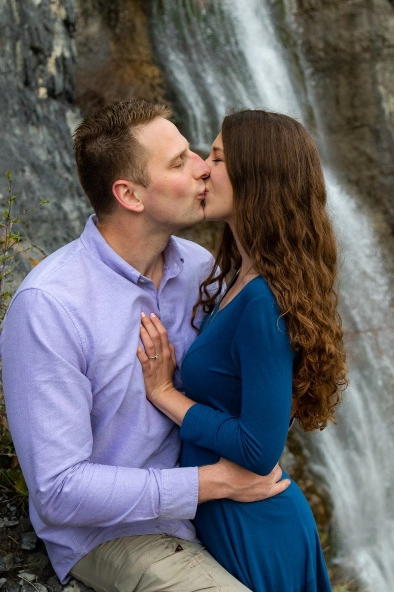 couple kissing by a waterfall