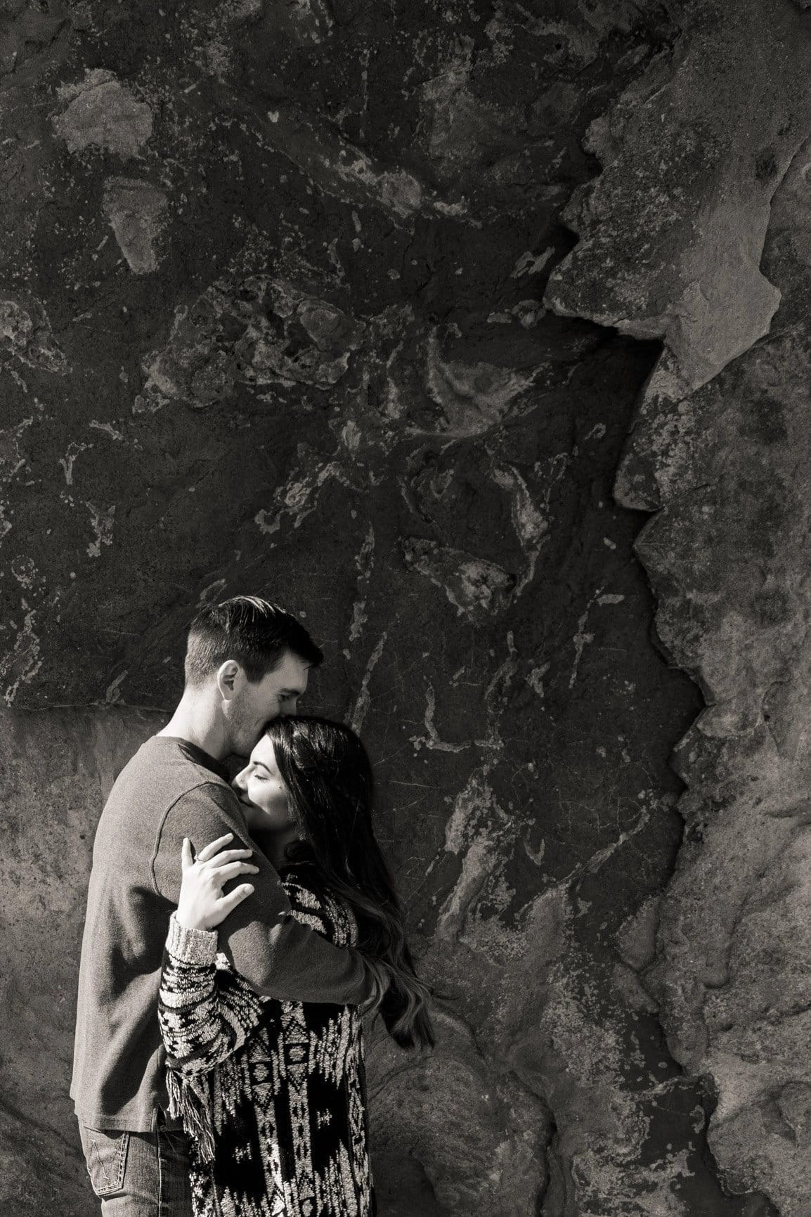 Beautiful people embrace at Garden of the Gods. An engagement session through this park left us in awe over the towering sandstone structures