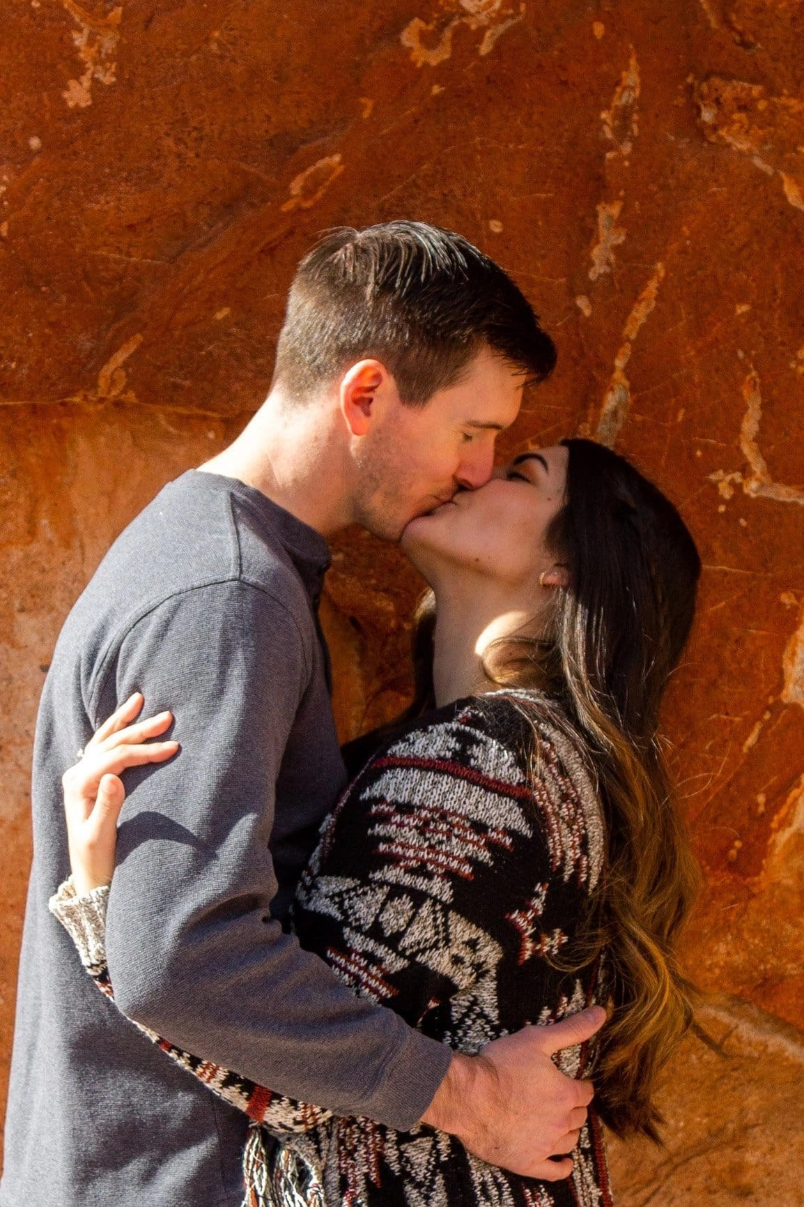 Engaged couple embrace and kiss at Garden of the Gods park in Colorado. Surrounded by red rock the couple was able to let go and be one with each other