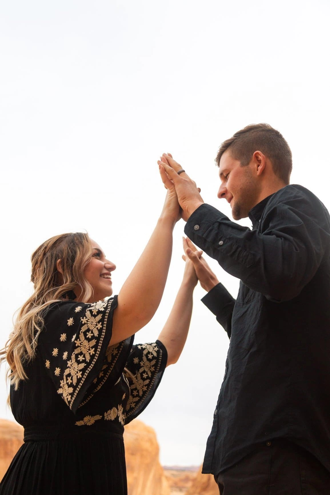 a couple form Utah smiles and presses palms while taking a break to connect