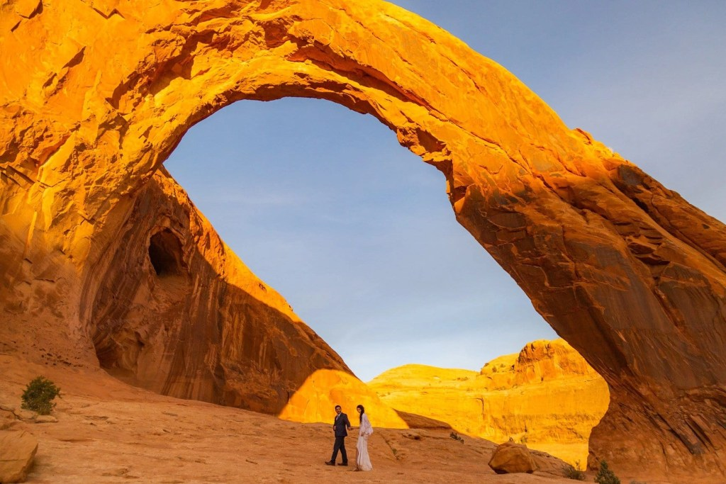 a couple walks under delicate arch in moab utah captured by their utah elopement photographer