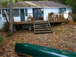 Exterior of a white cabin with a canoe in the foreground