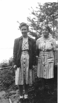 Two women standing in front of a lake