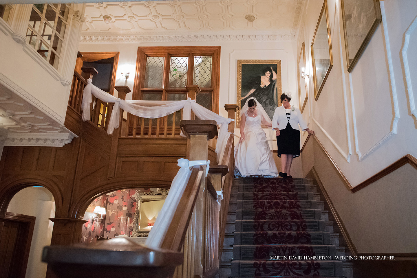 bride and mother of bride descending main staircase at nunsmere hall