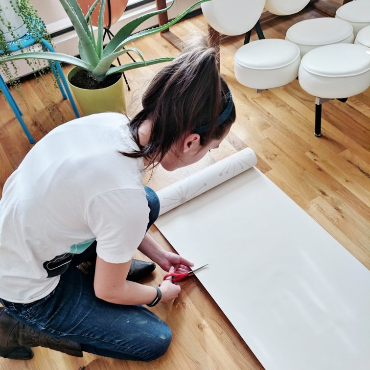 Cutting wallpaper and getting ready to hang wallpaper
