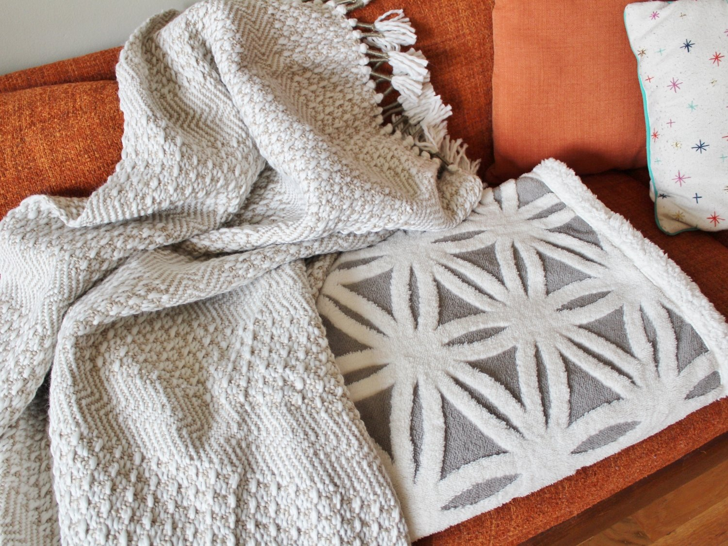 Cozy modern throw blankets on orange sofa