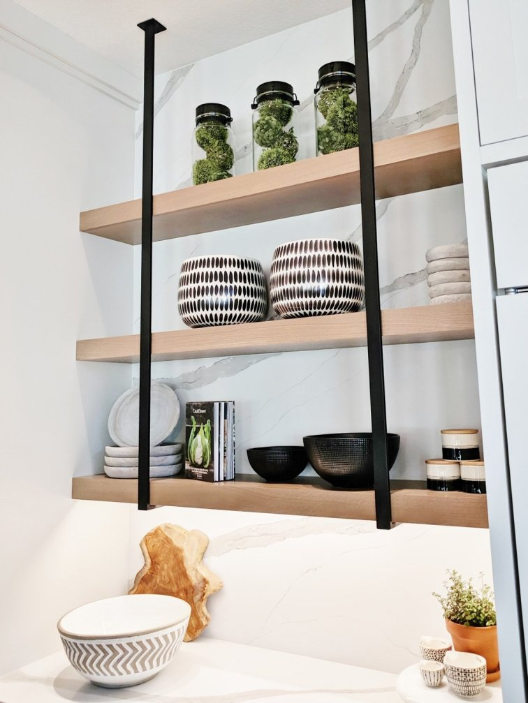 Modern open shelves in a kitchen with black, white and green decor