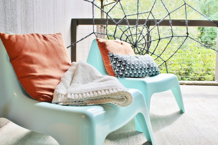 Add cozy mod outdoor seating with orange and black pillows.