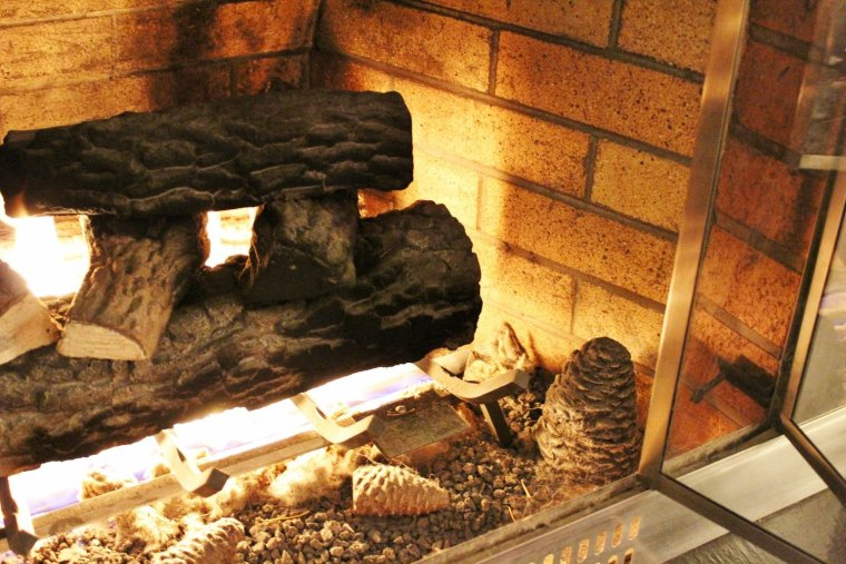 Modern gas fireplace with cozy log set and crackling pinecones