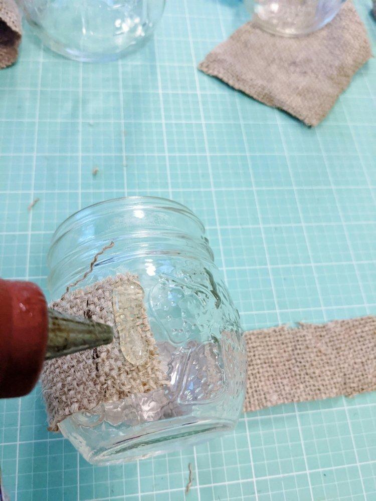 Gluing burlap to DIY candle holder lantern