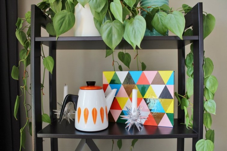Mid-century modern shelf display with Cathrineholm coffee pot and Eames book