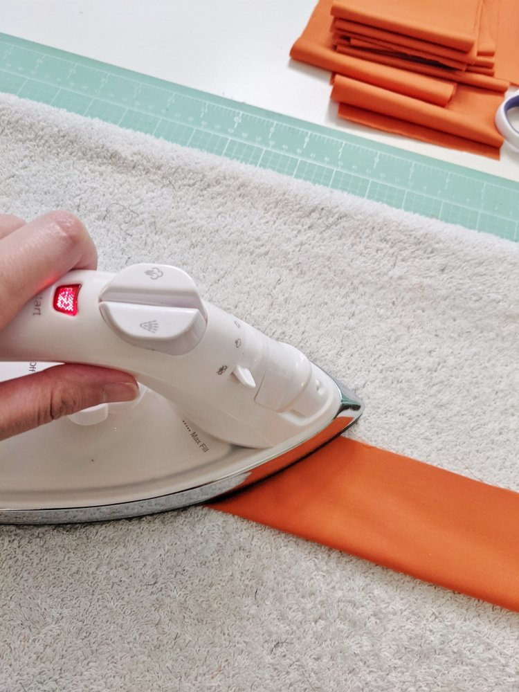 Ironing orange fabric strips to make Halloween cone trees