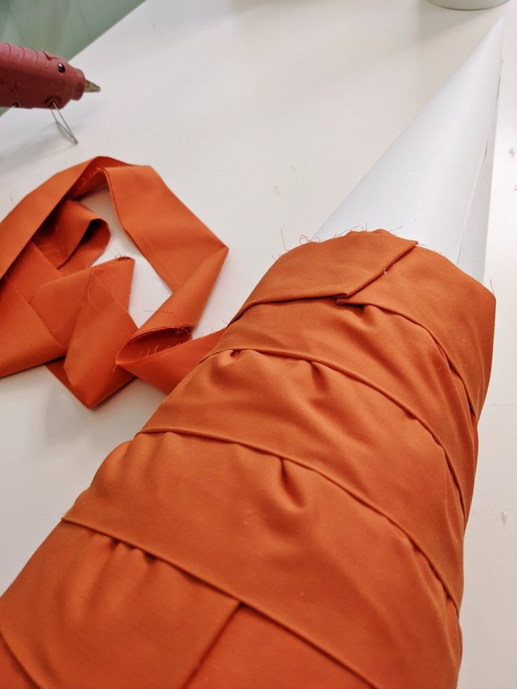 Gluing orange fabric to DIY cone tree