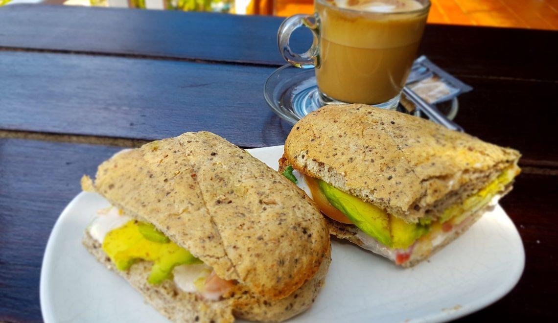 The delicious avocado sandwich and a cappuccino