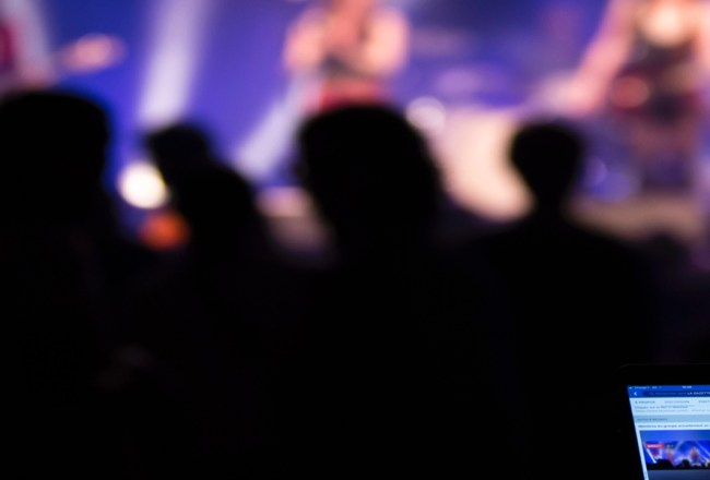 Call Out: Blurred image of a band on a stage beyond a crowd in shadow. A mobile phone with facebook open is held in the bottom right corner.