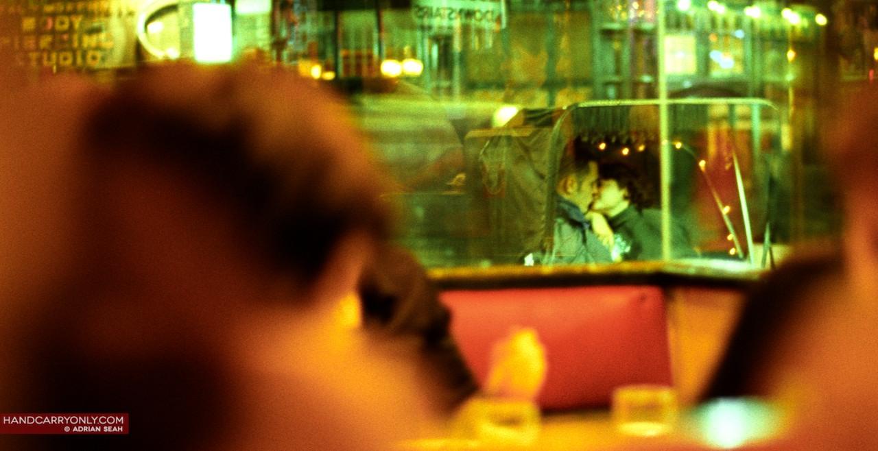 couple kissing outside restaurant window
