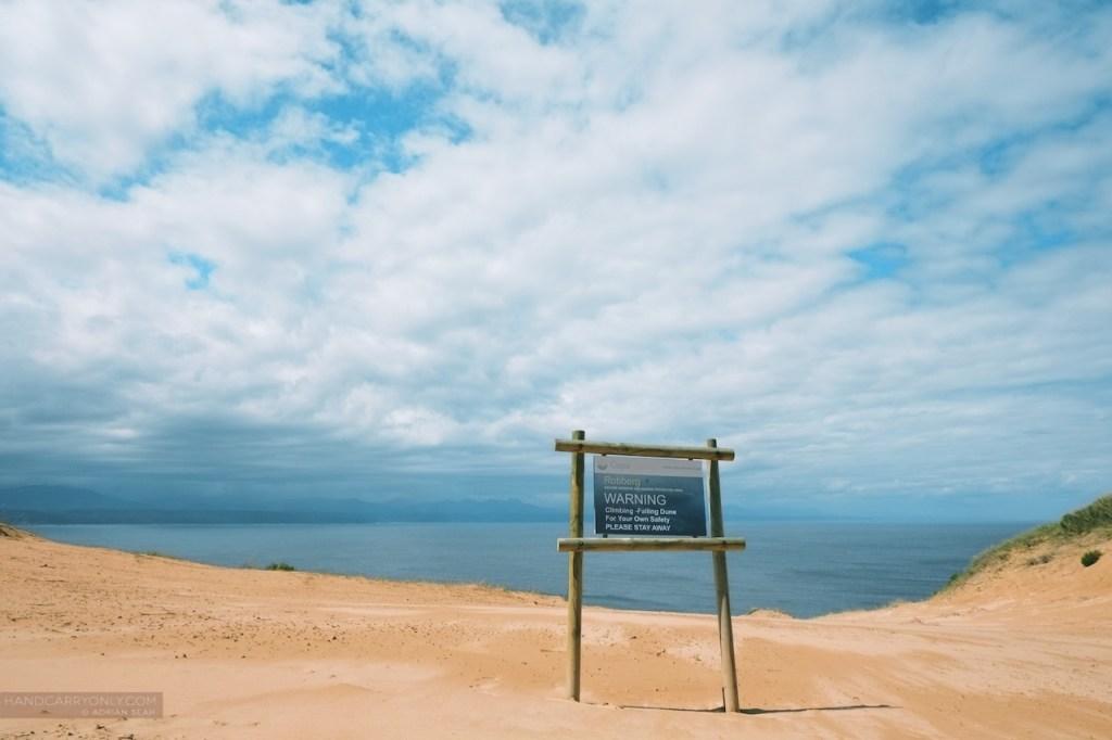 warning sign on witsand dunes robberg island
