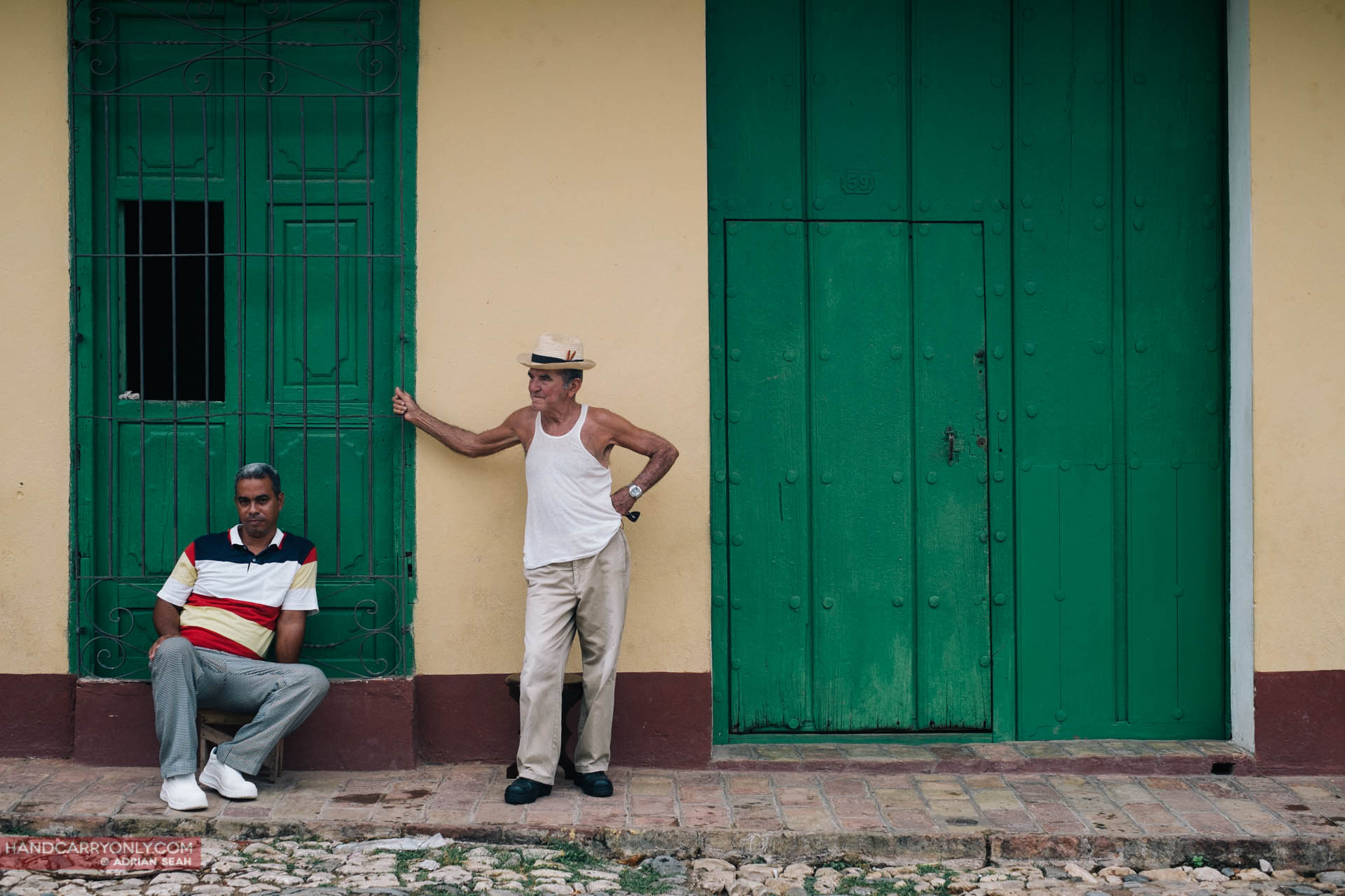 two men standing against wall trinidad cuba