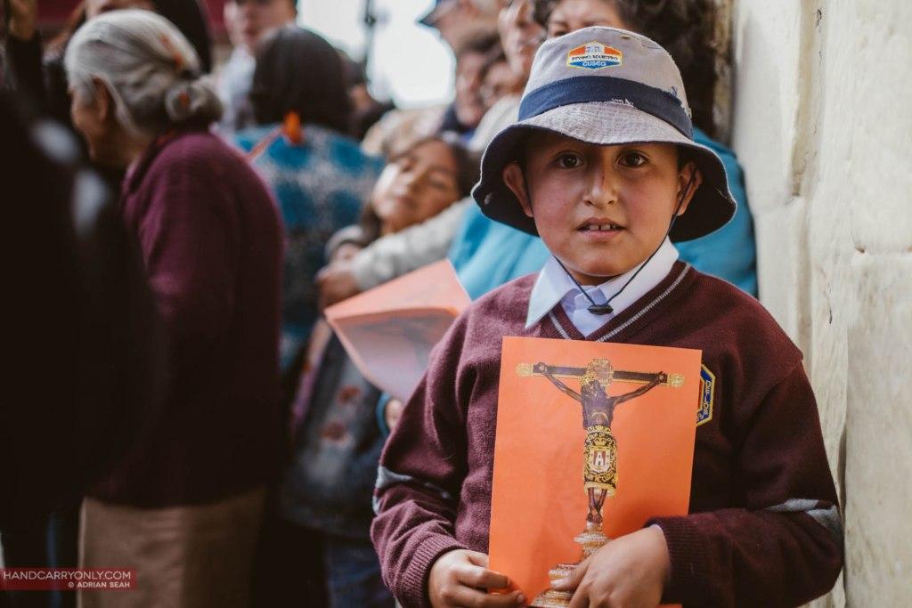 Little boy in the procession holding up a poster of a crucifix cusco peru