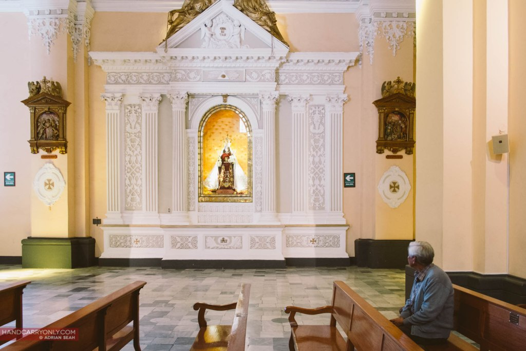 a devotee sitting in the pews of the basilica cathedral of arequipa