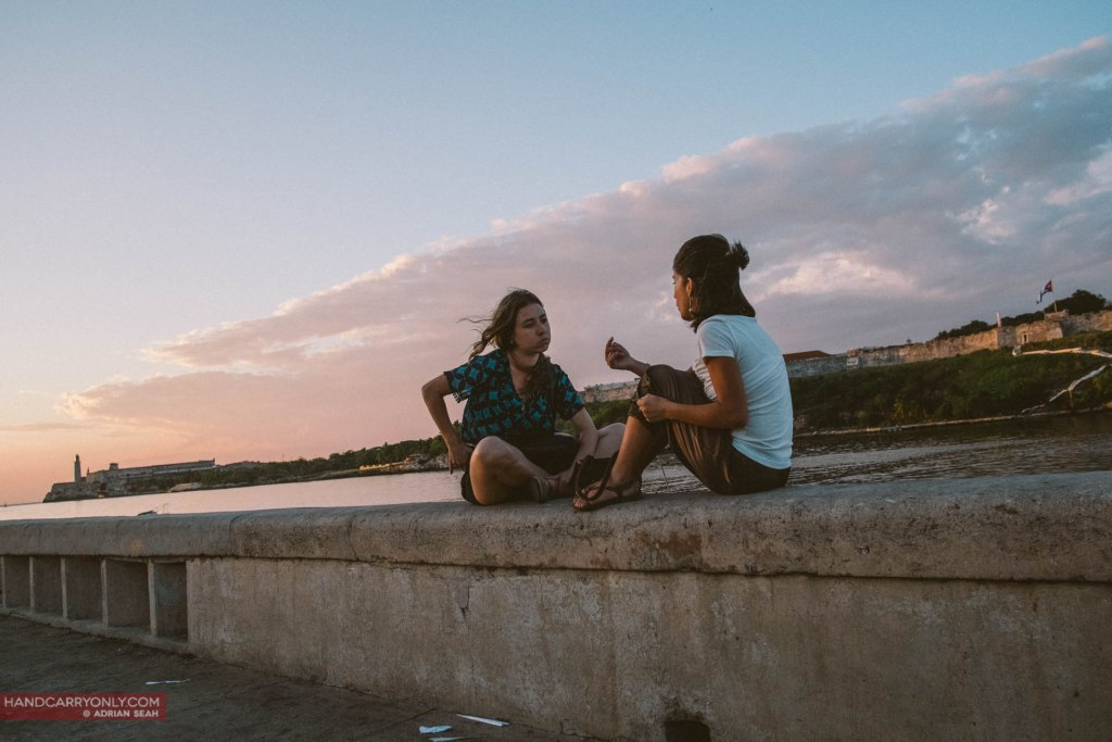Two friends sat chatting on the Malecon at sunset