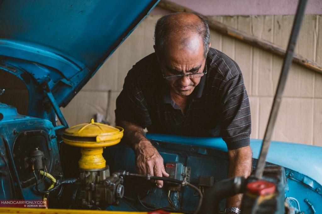 Man fixing vintage car vinales cuba