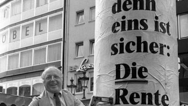 Arbeits- und Sozialminister Norbert Blüh klebt 1986 ein Wahlwerbeplakat auf.